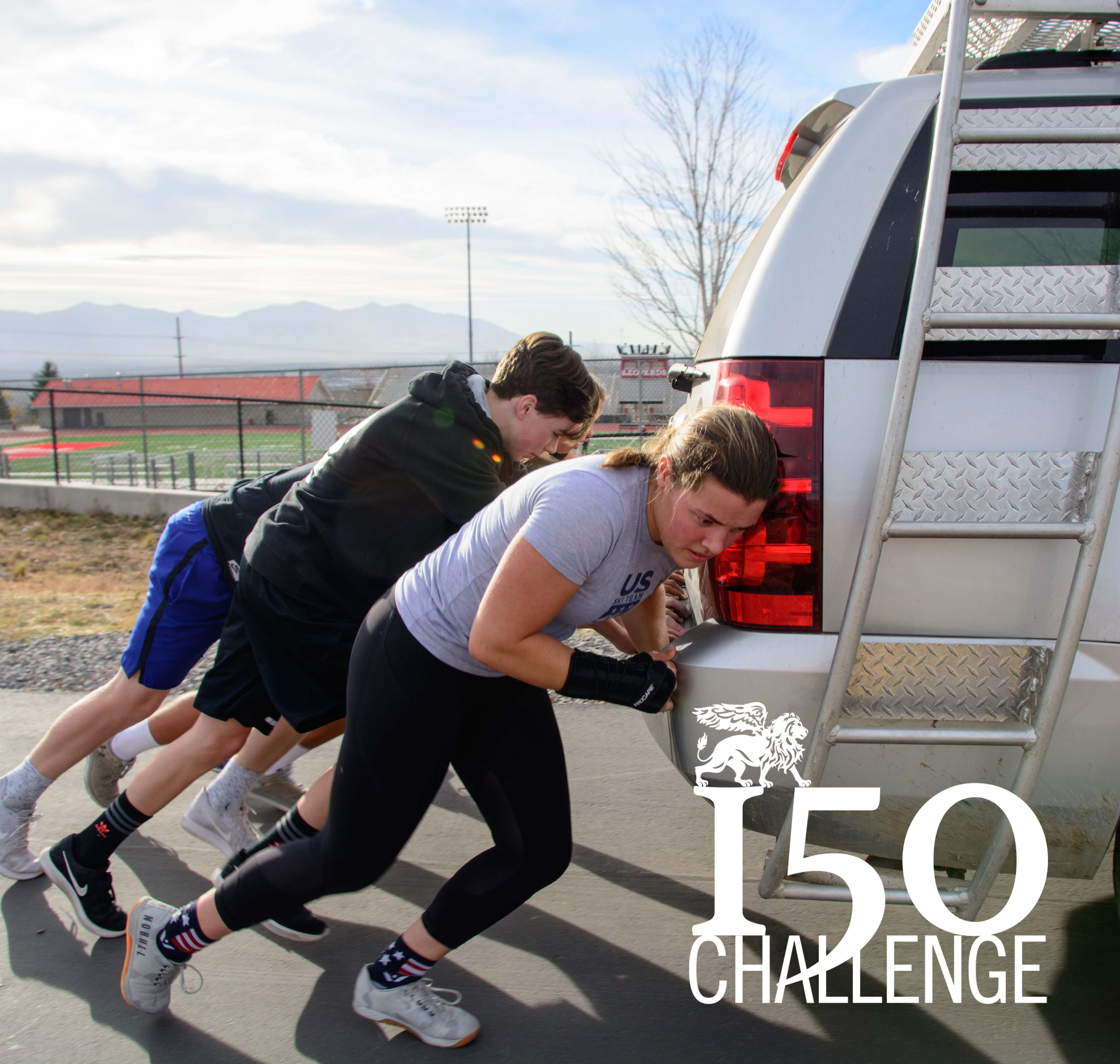 Students push a truck for the 150 challenge